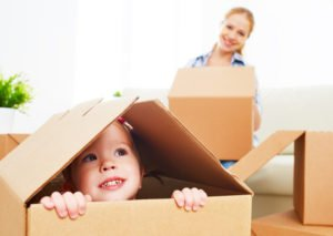 Moving economically, kid inside of the box, helping to pack