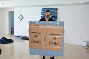Our manager Henry holding a picture frame, it is packed with blue pad and a box around it