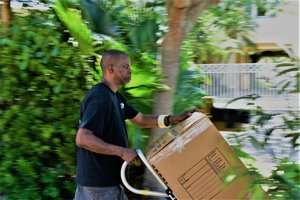 Sam handling two boxes with a silver hand truck