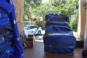 Armchair packed in a blue pad, movers getting ready to stack it
