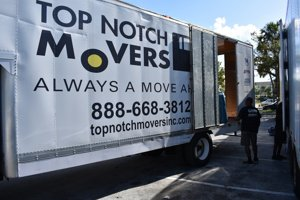 Long distance movers loading a 28ft Top Notch Movers truck